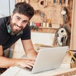 Young_man_at_online_customer_service_at_laptop._Computer_in_his_joinery