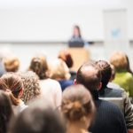 Female_speaker_giving_presentation_in_lecture_hall_at_university_workshop._Audience_in_conference_hall._Rear_view_of_unrecognized_participant_in_audience._Scientific_conference_event.