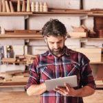 Artisan_woodwork_studio_with_shelving_holding_pieces_of_wood,_with_a_carpenter_standing_in_his_workshop_using_a_digital_tablet