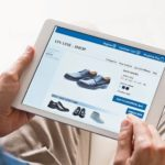 Young_man_looking_at_shoes_online._Man_looking_at_various_shoes_options_over_internet_through_digital_tablet._Casual_man_makes_online_shopping_at_home_with_digital_tablet.