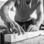 A_young_male_carpenter_builder_in_a_gray_T-shirt_and_working_overall_equals_a_wooden_bar_with_a_milling_machine_in_the_workshop,_in_the_background_wooden_boards