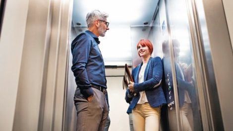 Two_business_people_in_the_elevator_in_modern_office_building.