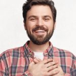 Positive_cheerful_bearded_male_has_pleasant_smile,_keeps_hand_on_heart,_expresses_his_good_feelings_to_close_people,_being_in_high_spirit_after_being_praised_by_someone,_isolated_over_white_wall