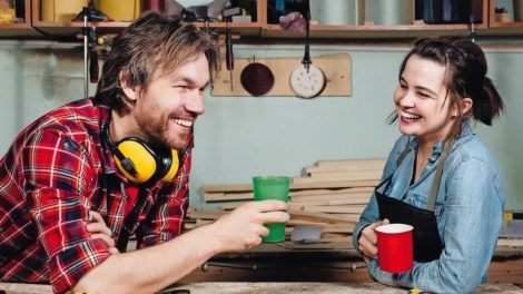 Man_and_girl_carpenters_having_break_from_indoor_work_in_wood_workshop._Coffee_time,_drink,_share_experiences,_discuss._Teacher_and_student._Laughing_smile.