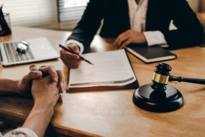legal_consultants,_notary_or_justice_lawyer_discussing_contract_document_with_laptop_computer_wooden_judge_gavel_on_desk_in_courtroom_office,_business,_justice_law,_insurance_and_legal_service_concept