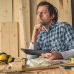 Carpenter_using_digital_tablet_in_small_business_woodwork_workshop_for_planning_a_new_DIY_project