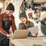 Positive_man_and_woman_in_aprons_standing_near_table_with_laptop_and_discussing_ideas_for_project_while_working_together_in_professional_carpentry_workshop