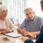 Senior_man_and_woman_meeting_medical_adviser_for_health_insurance_at_home._Old_couple_planning_their_investments_with_financial_advisor_after_retirement_at_home._Aged_couple_consulting_with_insurance_agent_while_sitting_together_with_prospectus_at_home.