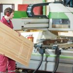 Manufacture_process_of_carpenter_work_with_wood_door_at_machining_center_during_furniture_manufacture