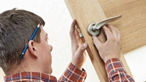 Male_worker_handyman_carpenter_at_lock_installation_into_wood_door