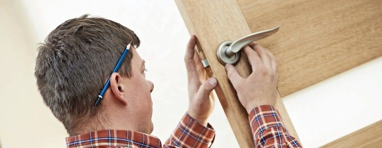 Male_worker_handyman_carpenter_at_lock_installation_into_wood_door