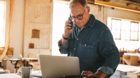 Senior_man_talking_on_cell_phone_and_using_laptop_on_work_table._Mature_carpenter_working_on_laptop_and_answering_phone_call_in_his_carpentry_workshop.
