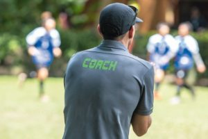 Male_soccer_or_football_coach_in_gray_shirt_with_word_COACH_written_on_back,_standing_on_the_sideline_watching_his_team_play,_good_for_sport_or_coaching_concept