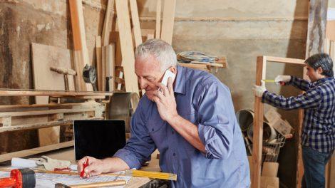 Senior_als_Chef_telefoniert_mit_Mobiltelefon_in_Schreinerei_Werkstatt