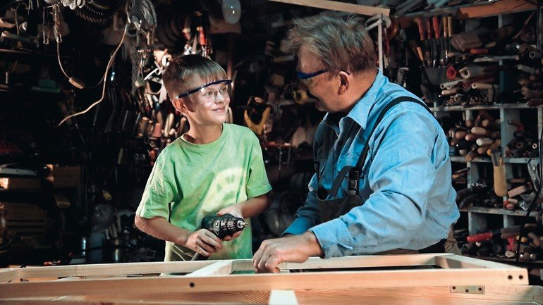 Young_boy_drilling_window_while_helping_grandfather_carpenter_in_workshop.