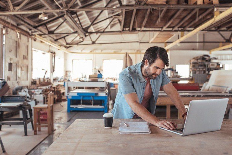 Young_woodworker_with_a_beard_leaning_over_a_workbench_in_his_large_workshop_full_of_carpentry_equipment_working_online_with_a_laptop