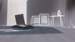 Laptop_on_cushion_and_wooden_floor_in_a_modern_room