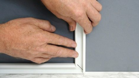 Handyman_installing_surface_mount_channel_for_electric_wiring