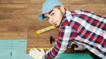 Carpenter_worker_installing_laminate_flooring_in_the_room