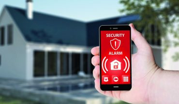 60013535_-_hand_hold_a_phone_with_security_alarm_app_on_a_screen_on_the_background_of_a_house.