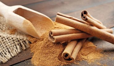 24551427_-_cinnamon_sticks_and_cinnamon_powder_in_wooden_scoop,_on_table