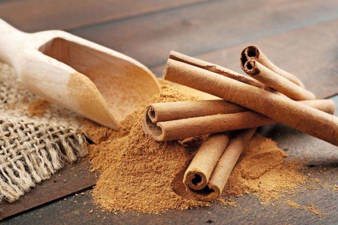 24551427_-_cinnamon_sticks_and_cinnamon_powder_in_wooden_scoop,_on_table