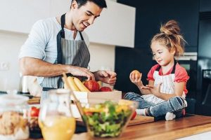 Young_man,_small_girl_and_healthy_food_in_a_domestic_kitchen.