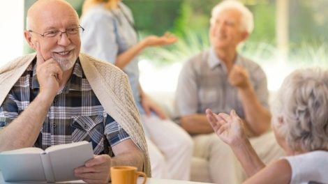 Smiling_man_in_glasses_holding_a_book_and_talking_to_woman_in_wheelchair